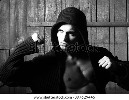 Sexual free stylish strong flexible muscular young macho man with bare torso in sweater standing indoor looking up on wooden background, vertical picture
