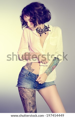 Sexual girl alluring in denim shorts and a white shirt. Beauty, fashion. - stock photo
