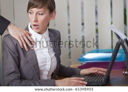 sexual harassment - surprised woman looking at the hand on her shoulder - stock photo