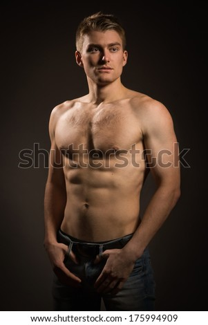 Sexual muscular man posing over dark background