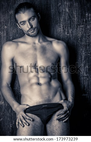Sexual muscular nude man posing over dark background. Black-and-white photo. - stock photo