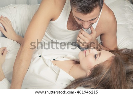Sexual scene of gentle and affectionate young couple in the bedroom