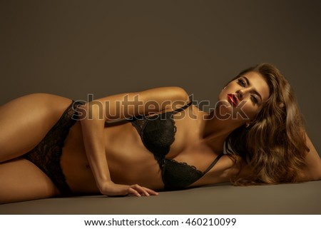 Sexual slim young woman in black underwear lying on the floor. Underwear fashion. Body, skin care.
