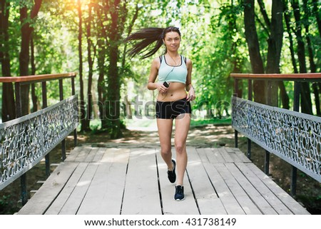 Sexual sports girl runs in park and listening to music