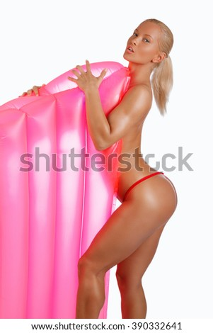 Sexual topless woman posing with a pink water matress. Isolated on a white background. - stock photo