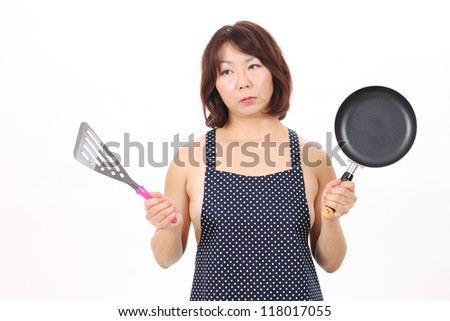 Sexual woman in apron with frying pan - stock photo