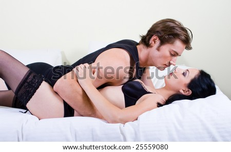 sexual young couple in bed - stock photo