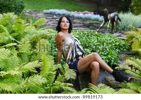 Sexual young pretty woman is sitting near to bush of fern in central park against sculpture of horse at Bastion hill in Riga, Latvia - stock photo