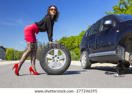 Sexually dressed woman repairing car.  Female body dressed erotic tights red miniskirt rolling spare tire to her broken car highway stop outdoor blue sky sunny day - stock photo