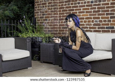 Sexy african american gothic woman smoking. Sitting on a couch outdoor patio, space for text. - stock photo