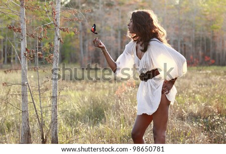 Sexy African American plays with a butterfly in the woods - stock photo