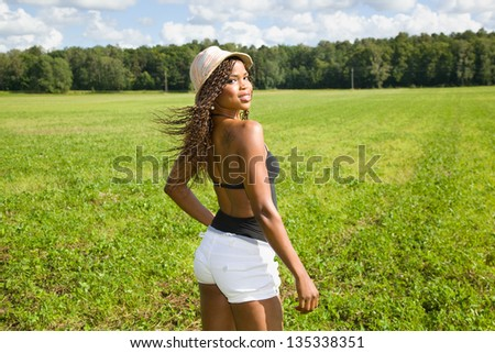 Sexy African American woman posing on a field - stock photo