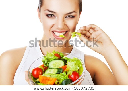sexy agressive woman biting salad on white background - stock photo