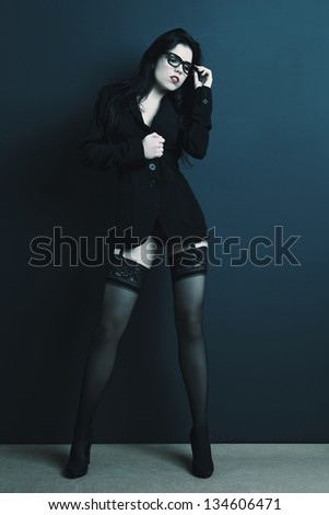 Sexy and attractive businesswoman in lingerie over a grey background - stock photo