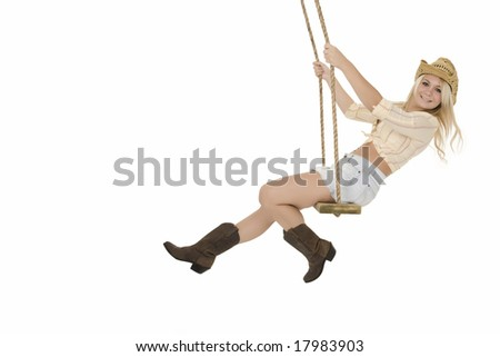 Sexy and beautiful Caucasian blond cowgirl playing on a wooden swing isolated on a white background