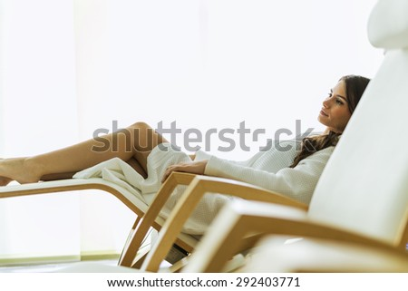 Sexy and beautiful woman relaxing peacefully in a chair dressed in a robe - stock photo