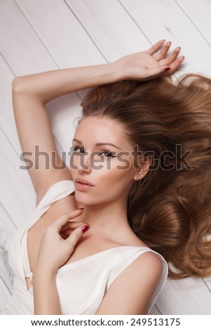 Sexy and Beautiful Woman with long Hair lying on the wooden floor - stock photo