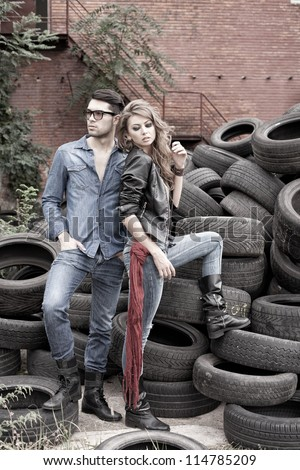 Sexy and fashionable couple wearing jeans, shoot in a grungy location - landscape orientation with copy-space - stock photo