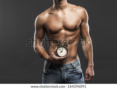 Sexy and handsome young man holding a clock over his belly - stock photo