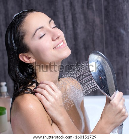 sexy and happy young beautiful woman taking a shower - stock photo