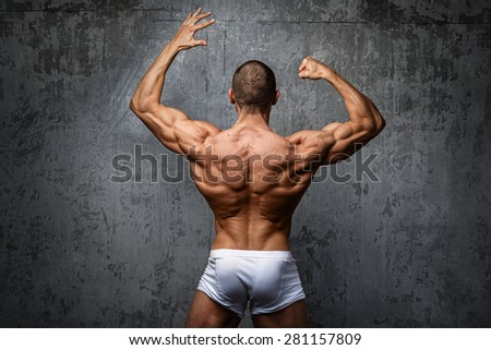 Sexy and muscular man  posing against stone wall