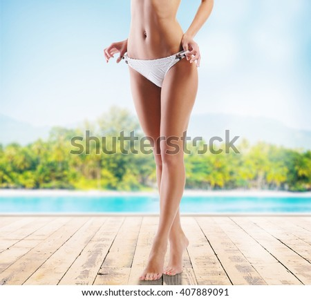 Sexy and sporty female body. Girl with a perfect shape on a summer beach. Sea, sky and beach background. Sport and diet concept. - stock photo