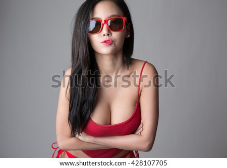 Sexy asian girl wearing red shirt and red underwear, wearing sunglasses. - stock photo
