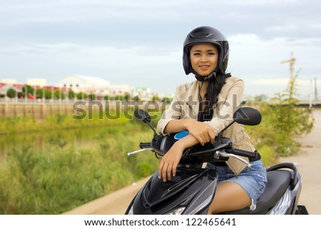 sexy asian girl with mini skirt, helmet, motorcycle in cambodia - stock photo