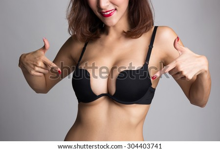 Sexy asian woman showing and pointing at her breast in black bra or  lingerie - stock photo