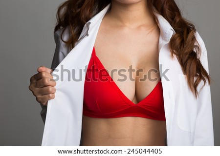 Sexy asian woman showing her sexy breast in red lingerie with shirt opened by hand on white background - stock photo