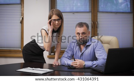 Sexy assistant and her boss. The scene in the office, a respectable, gray-haired businessman and his attractive young secretary.  - stock photo