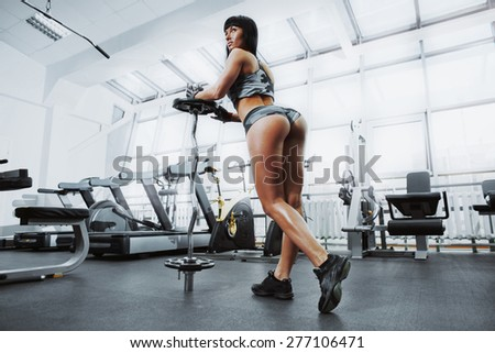 Sexy athlete woman posing with barbell in the gym