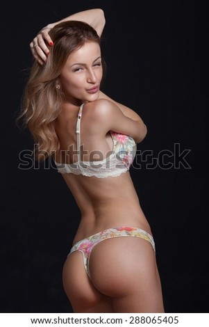 Sexy attractive blonde woman posing in elegant lingerie. Studio shot. Girl with long hair. Great ass. On black background. - stock photo