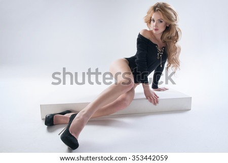 Sexy attractive blonde woman posing in fashionable dress in studio  - stock photo