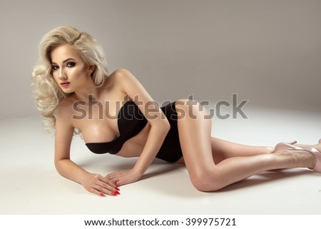 Sexy attractive blonde woman posing in fashionable lingerie in studio  - stock photo