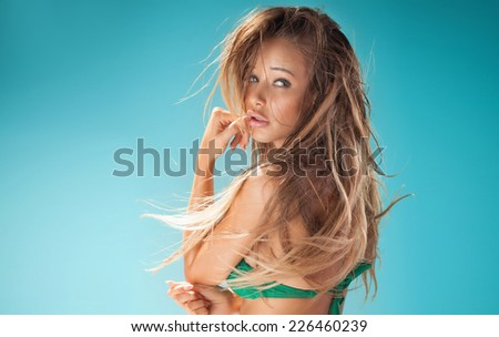 Sexy attractive blonde woman posing in fashionable swimsuit in studio, looking at camera. - stock photo