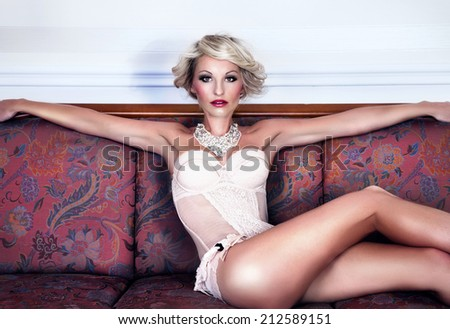 Sexy attractive blonde woman relaxing on couch, wearing sensual lingerie, looking at camera - stock photo