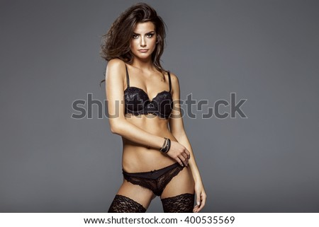 Sexy attractive brunette woman posing in fashionable lingerie in studio  - stock photo