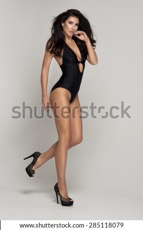 Sexy attractive brunette woman posing in fashionable swimsuit in studio  - stock photo
