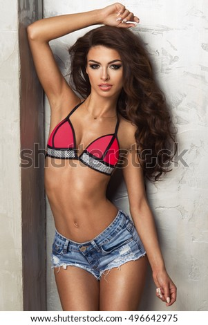 Sexy attractive brunette woman posing in fashionable swimwear in studio