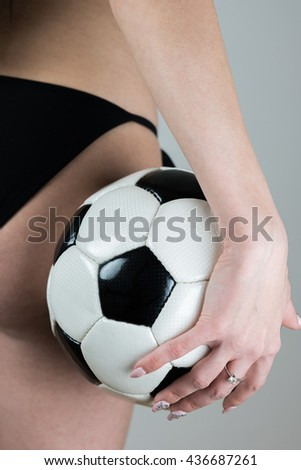 Sexy attractive Caucasian woman in bikini standing with a soccer ball. Rear view. Backside of a woman. Sexy football. - stock photo