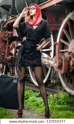 sexy attractive girl waiting for landing on the platform in the vintage train.Vintage woman in twenties style waiting for the train.Retro-styled woman with suitcase on the platform waiting for train