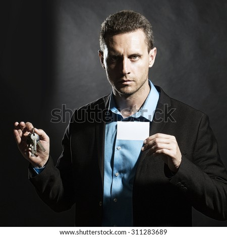 Sexy attractive unshaven young business man in jacket and blue shirt holding white visiting card and keys bunch in hands looking forward standing on black studio background copyspace, square picture - stock photo