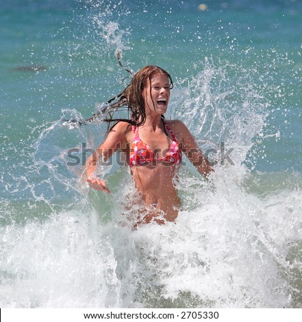 Sexy attractive young girl in red bikini being splashed by cold wave in the sea whilst on holiday or vacation