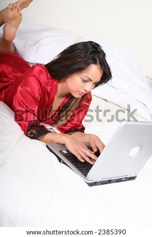 Sexy Attractive Young Woman Relaxing in Bed With Laptop Computer - stock photo