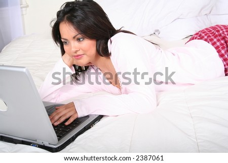 Sexy Attractive Young Woman Relaxing in Bed With Laptop Computer