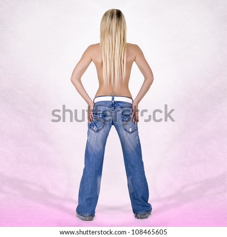 Sexy back of a blonde head woman wearing jeans on pink background - stock photo