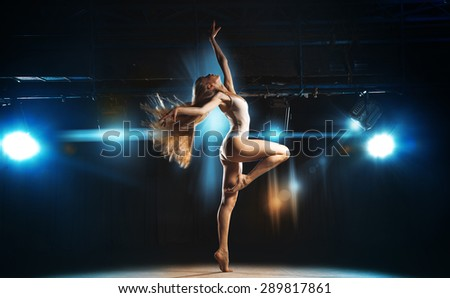 Sexy ballerina on stage posing against the backdrop of the spotlight in theater - stock photo