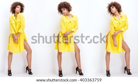 Sexy beautiful African American girl posing in yellow fashionable dress. Woman with afro and glamour makeup. Studio shot. - stock photo