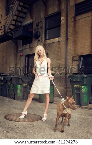 Sexy, beautiful blond woman with brown pit bull terrier dog on a leash in grungy urban alley, trashcans in background; slight cross-processing - stock photo